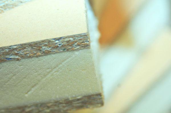 Priečka TETRA K z dreveného nosného rámu, na ktorom sú z oboch strán uchytené panely hrúbky 6 cm a časti drevenej konštrukcie zakrývajú vonkajšie obkladové dosky z recyklovaných obalov tetrapak. (KURUC Company)
