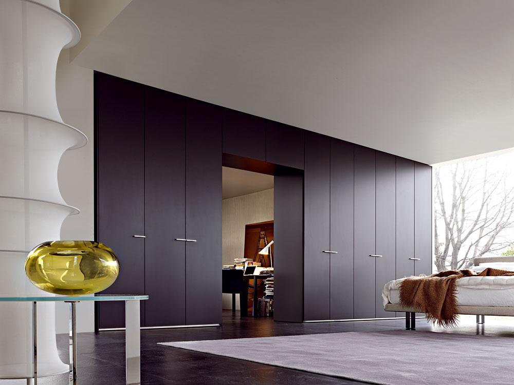 Umiestnenie šatníkovej skrine pri stene, kde sa nachádzajú dvere do miestnosti, sa rieši pomerne často. Ponúkame inšpiráciu, ako na to, aby výsledok pôsobil elegantne aprirodzene zapadol do priestoru. Netreba zbytočne kombinovať aprispôsobovať materiály, použite rovnaký materiál na obalenie celej konštrukcie, prípadne aj na dvere. Elegantné, decentné avkusné.