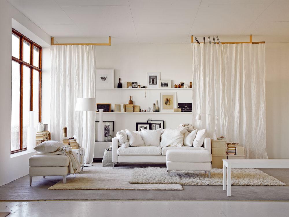 Závesy pred policami zjemňujú interiér jednoduchej obývacej izby apridávajú jej šmrnc. Občas aj ukryjú niečo, čo nemá byť na očiach. Hra stextilom vpriestore prináša do interiéru mäkkosť aútulnosť.
