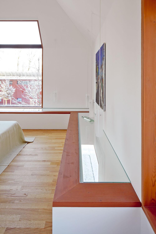 Zasklená lavica lemujúca spálňu vytvára dojem levitujúcej podlahy. Osvetlenie spustené nízko nad lavicu spálňu jemne dekorujeazároveň pôsobí ako svetelný efekt na stropeobývacej izby.
