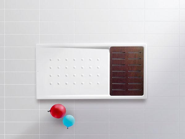 Keramickú sprchovaciu vaničku Walk-in s rozmermi 140 × 70 cm od značky Roca môžete doplniť roštom z exotického dreva. Cena vaničky je 483,50 €, rošt z dreva Wenge, Zebrano alebo Orange stojí 185 € a sifón 54,80 €.