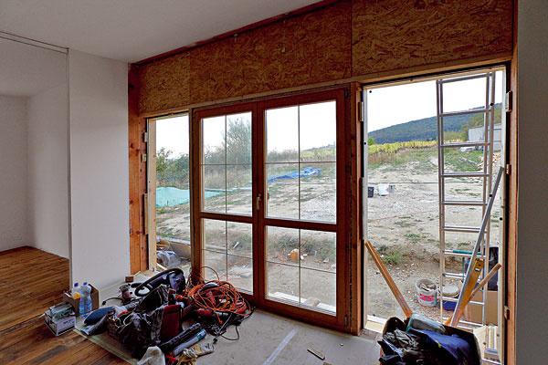 """Zbazáru Aby dosiahol prepojenie sokolitou prírodou, rozhodol sa architekt osadiť okná oniečo nižšie tak, aby mal cez ne výhľad aj vtedy, keď sedí na podlahe. Museli však spĺňať tri základné podmienky – byť lacné, drevené asizolačným dvojsklom. """"Drevené okná sú úžasné vtom, že sa dajú recyklovať či použiť viackrát. Za všetky okná, ktoré vdome máme, sme zaplatili 500 €, čo je vporovnaní so zákazkovými oknami ušetrených približne 3 500 €. Tieto okná sme si narezali arozmerovo prispôsobili. Zpár kusov, ktoré sme kúpili, sme vytvorili okná takmer do celého domu,"""" hovorí hlavný recyklátor, architekt Tesák."""