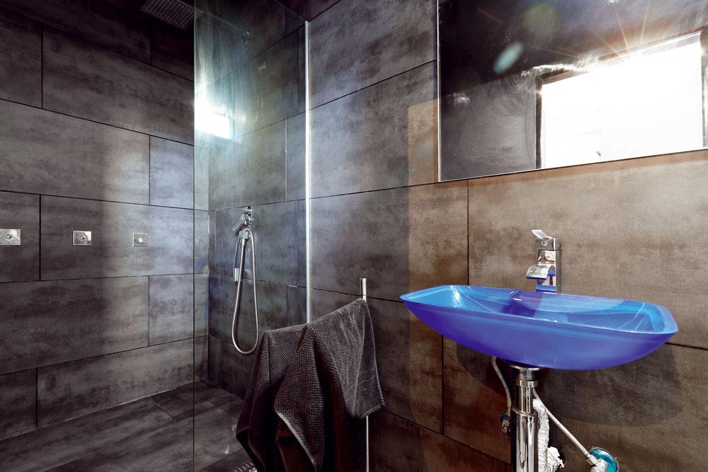 """""""Šeď"""" stroho poňatej kúpeľne oživuje žiarivo modré umývadlo, ktoré zrána zaručene prebudí každého spachtoša."""