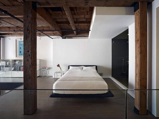 Spálňa v bielom odtieni kontrastuje s tmavou drevenou konštrukciou.