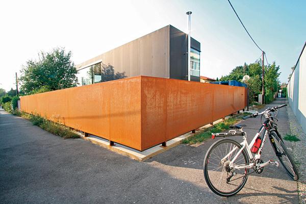 Nezvyčajný materiál azaujímavý farebný kontrast splotom, ktorý dopĺňa charakter domu ajeho fasády. Kovový plot so skorodovaným povrchom afasáda zkaučukovej fólie, ktorá sa bežne používa ako hydroizolácia pri vytváraní záhradných jazierok. Nezvyčajný neoprénovy vzhľad nás skutočne zaujal. (foto: Pichlerarchitekten, autor projektu: Günter Pichler)