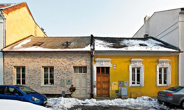 Príklad výborného vkusu majiteľov domu vľavo acitu pre detail, farbu ašarm vkontraste so susedným domom vpravo. Neprekážala by nám odpadnutá pôvodná výzdoba ahorší stav fasády, katastrofou je však jej farebnosť, tá ju úplne ničí.