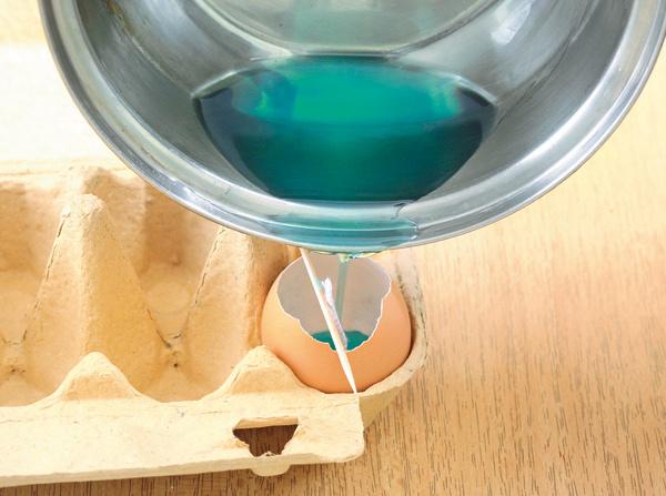 3.Vo vodnom kúpeli roztopte asi 4 veľké lyžice vosku, potom pridajte farbu aarómu. Farby stačí len malý kúsok. Či ste sodtieňom spokojní, zistíte kvapnutím vosku na bielu dlaždicu alebo inú bielu plochu. Roztopený vosk lejte do vajíčka na trikrát, každú vrstvu nechajte najskôr stuhnúť. Ak by ste naliali všetok vosk naraz, stred sviečky by sa prepadol, pretože hmota sa po vychladnutí zmrašťuje.
