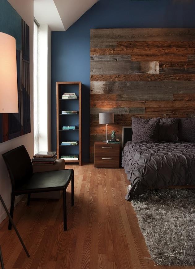 Postele sa nemusíte ani dotknúť, a predsa z nej bude dominanta miestnosti. Postarajte sa o priestor za ňou. V tomto prípade pokračuje drevená obkladová sága. Stačí istý stupeň kontrastu s posteľou a okolitou stenou – teplé odtiene hnedej verzus sýta studená modrá a sivá. Štýlová podpora obkladu zo strany podlahy a majiteľ môže byť spokojný. Jednotlivé prvky si navzájom okresávajú hrany a dopĺňajú sa.