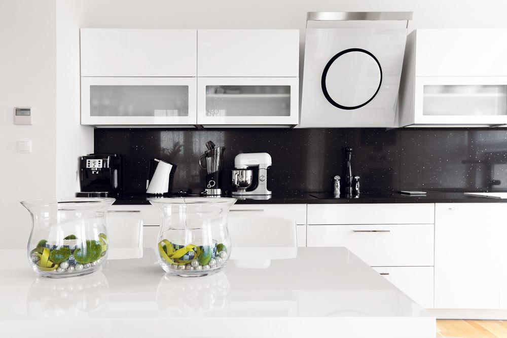 Vspodnej časti linky je okrem obligátnej umývačky riadu aj práčka (oboje za dvierkami včasti pri okne), zvyšok tvoria praktické zásuvky vybavenéprvkami na uloženie tanierov, pokrievok, príborov... Pekným azároveň praktickým detailom sú horné skrinky so svetelnými dnami – svetlo dopadá nielen na pracovnú plochu, ale osvetľuje aj vnútro skrinky. Preto sem vybrali dvierka zmliečneho skla, aby siluety pohárov, šálok aďalšieho vybavenia decentne oživili inak jednoduchú kuchyňu.