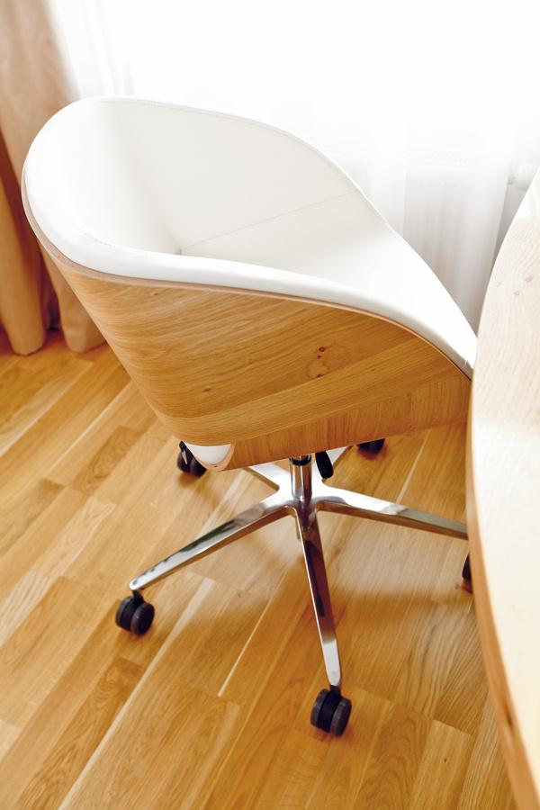 Kpracovnému stolu doplnili sympatické kresielko so zaujímavým dizajnom – dyhovaný korpus je skombinovaný skoženým čalúnením. Pôvodne zvažovali podobný odtieň kože, ako má sedačka, nakoniec sa však rozhodli zladiť ju radšej spracovnou zostavou.