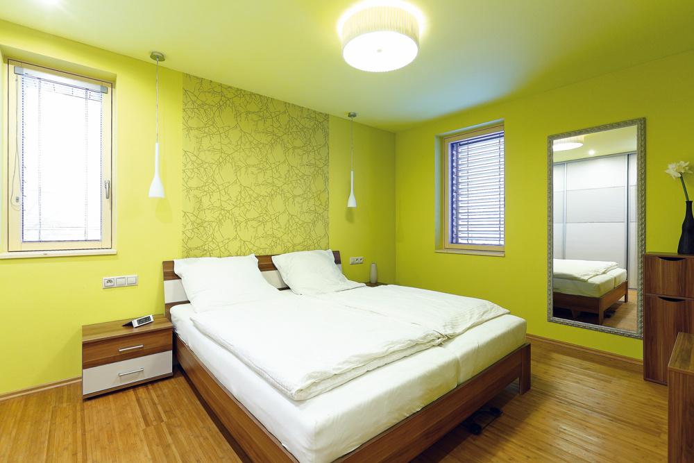 Nábytok vspálni je jediný, ktorý si mladí manželia priniesli zpredchádzajúceho bývania. Knemu architektka pridala osvedčený šatník aelegantné svietidlá. Celok potom osviežili zelené steny.