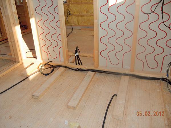 """Okrem núteného vetrania srekuperáciou, ktoré spolu sdôkladnou izoláciou obvodových konštrukcií minimalizuje únik tepla zinteriéru, je vdome aj stenové vykurovanie – voda ohriata tepelným čerpadlom sa privádza do rozvodov vsadrokartónových paneloch. Vykurovací okruh slúži aj na letné chladenie – dokáže znížiť teplotu vinteriéri oasi 2 °C. """"Keď chceme do stien vŕtať, musíme byť opatrní anajskôr si zistiť, kde presne sú rúrky,"""" upozorňuje domáci pán."""