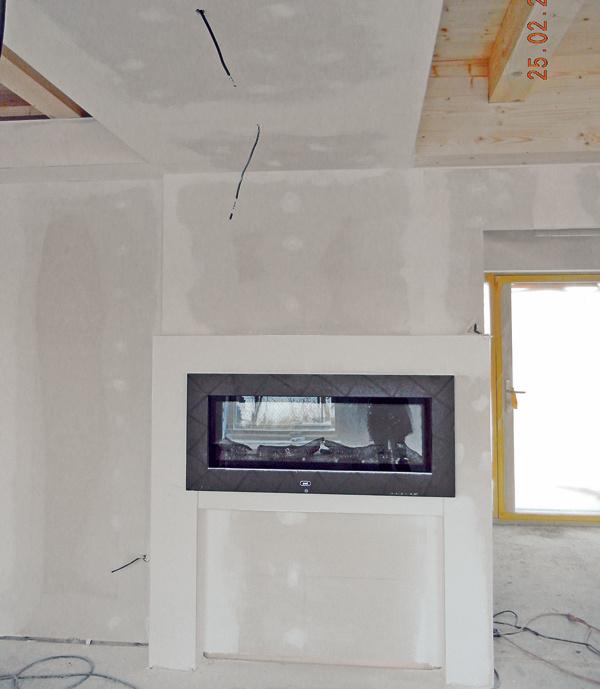 Kozub museli zabudovať do obývačkovej steny hneď vpočiatočnej fáze dokončovacích prác.