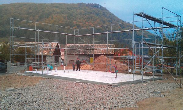Okolo hotovej betónovej dosky vyrástlo lešenie potrebné na montáž drevených panelov vysokých cez dve podlažia.