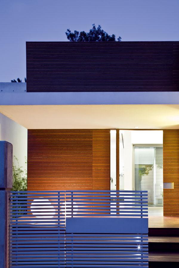 Sprecízne zladenými detailmi, napríklad vstupnej bránky, dverí aobkladov strednej časti domu ažalúzií na sklenej stene vobývacom priestore dlhej štrnásť metrov, sa stretávame vcelom dome. Vedľa vstupu sú rozložené polyetylénové guľové svietidlá od talianskej firmy Globo, ktorých variant AquaGlobo pláva aj vreflexnej nádrži.
