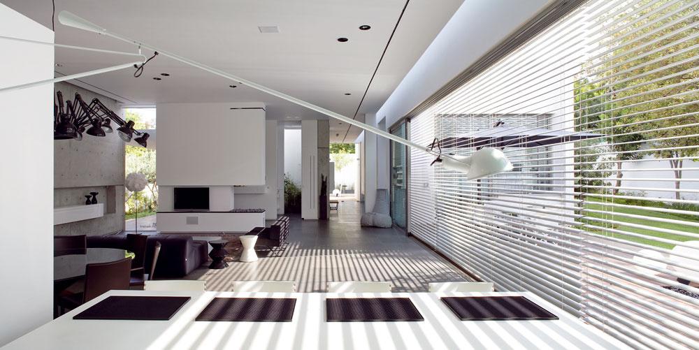 Snímka dokladá odlišnosť pohľadových osí, ktoré architektka nazýva vizuálne koridory – stredný ústi do sporo osvetleného úzkeho dvora. Katmosfére prispieva neosvetlená západná stena obrátená do ulice. Východnej pri dlhom okne dodáva ešte viac svetla svetlík.  Pred oknom obráteným kvstupu stojí lampa Knueller zpokrčeného papiera asklolaminátu (Ingo Maurer, 2004) od Bernharda Desseckera, vpopredí je nad raňajkovým stolom vysunutá nástenná lampa 265 od Paola Rizzata (Flos, 1973).