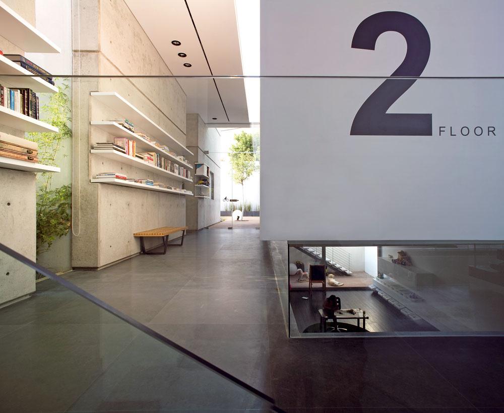Vyvýšená spálňa umožnila vytvoriť pri päte múru sklený sokel, cez ktorý prúdi svetlo do dolného obytného priestoru, momentálne slúžiaceho ako herňa. Police, ryhy vmúroch asvetlo rozptýlené laminovaným mliečnym sklom svetlíka vytvárajú silné horizontály, ktoré zmierňuje vysoký priechod do dvoch detských izieb asklené steny – vľavo odkrýva pohľad do úzkeho dvora svysadeným bambusom (Bambusa multiplex), doprostred terasy vybrali rohovník (Ceratonia Siliqua) splodmi známymi ako svätojánsky chlieb. Na sklených dverách na terasu upúta piktogram bicykla – vedľa je naozaj miesto na ich uloženie.
