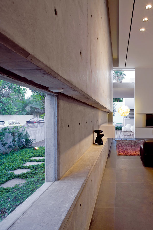Podobne ako ryha na priečelí pokračuje výrez tvoriaci horizontálu na najbližšom rovnako orientovanom betónovom múre – vchodbe severného krídla (obr. 11). Tu, vobývacom priestore, je vo výreze umiestené okno na výhľad od jedálenského stola. Opačnú os tvorí okno vrohu miestnosti obrátené kvchodu. Pretínajúce sa osi sú kľúčovým prvkom dizajnu domu.  Chodníky, aké vidíme vpodraste zbrečtanu, už dlho inšpirujú architektov vjaponských čajových záhradách rodži.