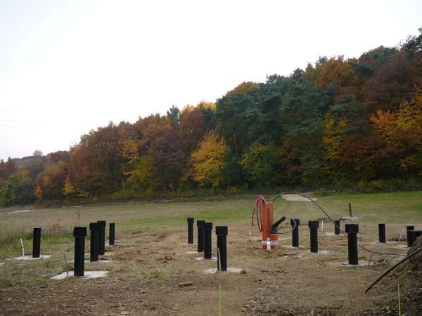 Dom musí stáť na pätkách  Vblízkosti totiž tečie potok aslamená izolácia by sa nemala dostať do kontaktu s vlhkosťou. Zároveň sa tak obytné miestnosti dostanú bližšie kslnku, z tieňa neďalekého lesíka. Mohutné základové pätky vyrástli na pozemku koncom októbra 2011.