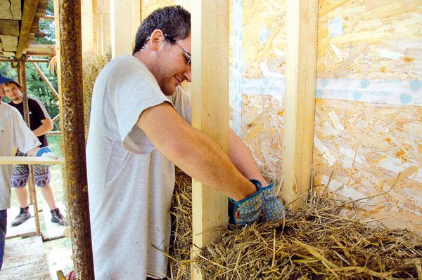 """Izolovanie slamou bolo najprácnejšou fázou stavby. Každý bal sa totiž musel skrátiť – vzdialenosť drevených stĺpikov vychádzala zo šírky drevovláknitých dosiek, ktorá je menšia než dĺžka balov. Okrem toho sa ich konce museli zarovnať aprípadné voľné miesta sa upchávali voľnou slamou, aby nevznikli izolačne oslabené miesta. Najneprístupnejšie časti konštrukcie sa vypĺňali ovčou vlnou. Našťastie na """"slamený workshop"""" prišlo veľa ochotných apracovitých mladých ľudí."""