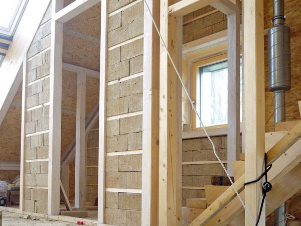 Interiér. Obvodové steny apriečky sú vyplnené nasucho ukladanými nepálenými tehlami, ktoré sú fixované dreveným latovaním. Vnútornú povrchovú úpravu vytvorí hlinená omietka. Masa hliny vo forme tehál aomietky plní funkciu akumulácie tepla aregulácie vlhkosti vinteriéri. Keďže drevené stĺpiky ostanú na niektorých miestach odkryté, dôležité bolo precízne vyhotovenie nosných prvkov.