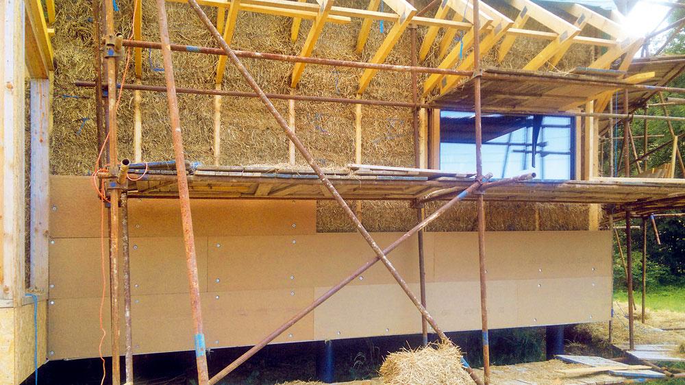 Ochrana bez fólie. Na drevený rošt sa potom priskrutkovali drevovláknité dosky Hofatex Kombi, ktoré slúžia ako ďalšia tepelná izolácia, azároveň chránia slamu pred vodou, mechanickým poškodením aškodcami. Drevovláknité dosky navyše bránia aj nepríjemnému letnému prehrievaniu – vďaka ich vysokej tepelnoakumulačnej schopnosti sa predĺži čas, za ktorý sa konštrukcia prehreje (aspoň do nočných hodín, keď sa dá interiér ochladiť vetraním).