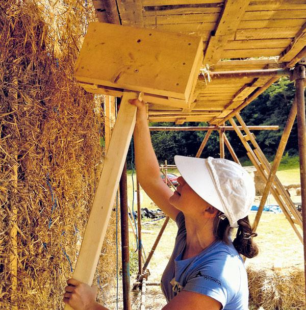 """Exteriér. Primárna tepelná izolácia domu je zo slamy. Slamené baly sa vtláčali do pomocnej drevenej konštrukcie (je určená na pripevnenie drevovláknitých dosiek). Baly museli byť medzi drevené stĺpiky vložené natesno aobčas bolo potrebné """"presviedčať"""" ich veľkým dreveným kladivom – """"presviedčadlom"""" alias """"Flinstonom""""."""