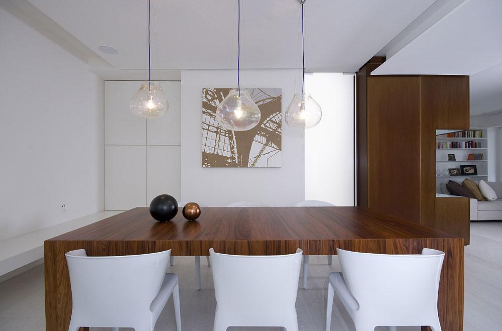 Vkúte jedálne sdominantným dreveným stolom je za bielymi dvierkami, akoby položenými na lemujúcej lavici, ukrytý príborník.