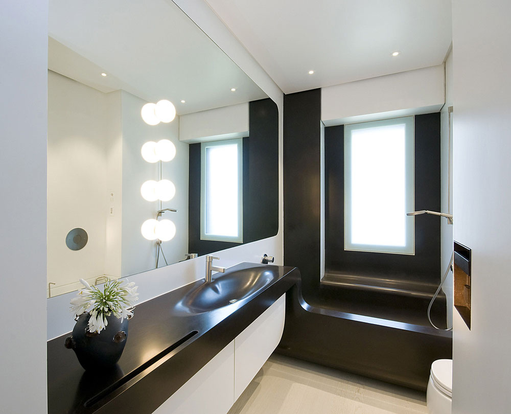 Kúpeľňa vdynamickom bielo-čokoládovom vyhotovení má zaujímavú vaňu, ktorá plní aj funkciu sprchovacieho kúta.