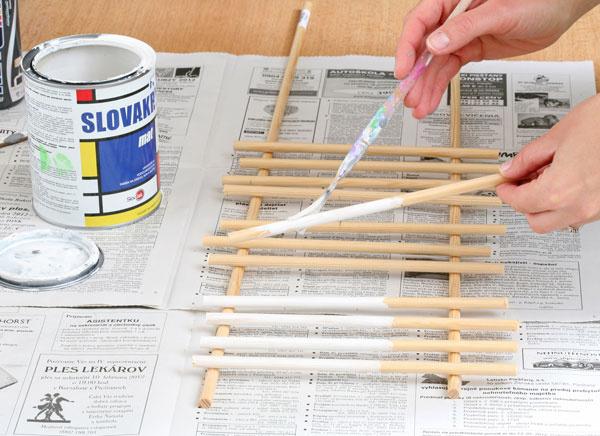 4. Nafarbite tyčky. Na drevených tyčkách si odmerajte asi 12 cm atúto časť vymaľujte bielou farbou (2 až 3 vrstvy). Zvyšnú časť nechajte čistú, lepšie na ňu chytí lepidlo.
