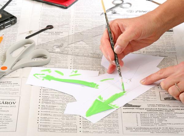 6. Vystrihnite ručičky. Zhrubého papiera vystrihnite hodinové ručičky. Na ich koncoch vystrihnite dierky také veľké ako na pôvodných ručičkách. Ručičky vymaľujte zelenou farbou.