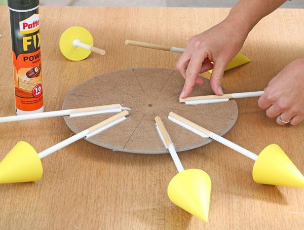 9. Nalepte tyčky na ciferník. Na druhú stranu sololitového kruhu naznačte 12čiar (môžete si pomôcť ciferníkom zpôvodných hodín) atyčky skužeľmi na ne presne prilepte lepidlom na drevo. Sololit musíte mať podložený podľa výšky kužeľov.