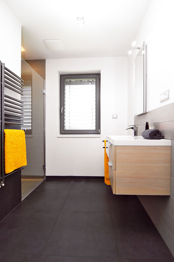 Elegantné kúpeľne, ktorých dizajn je založený na kombinácii rôznych formátov obkladov, sú farebne striedme.