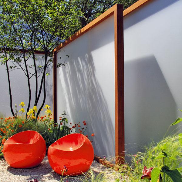 FLEXIBILNÁ ZÁHRADA. Záhrada nemusí byť len statická. Pomocou posuvných deliacich stien, ktoré čiastočne prepúšťajú svetlo, možno záhradu rozdeliť na niekoľko častí azískať tak priestor na rôzne činnosti – posedenie sblízkymi či domáce pracovisko. Výhodou takejto záhrady je, že nepôsobí nudne. Samozrejme, treba ju niečím ozvláštniť. Vtomto prípade sú výrazným prvkom oranžové sedačky zplastu, ktorý je vzáhrade opäť in. Tie farebne harmonizujú srámom posuvných stien. Sďalšími dominantne pôsobiacimi plochami to však už netreba preháňať.