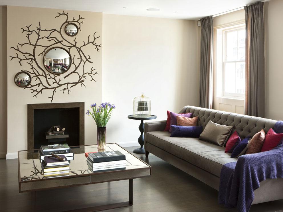 """Biele steny boli pri zariaďovaní tohto bytu tabu. """"Odtiene béžovej pôsobia teplejším dojmom a tvoria perfektné pozadie pre farebný nábytok, ktorý interiéru dodáva jedinečnosť,"""" hovorí Marie. Najlepšou inšpiráciou je podľa nej príroda: """"Nájdete v nej pestrú zmes farieb, veľkostí, tvarov a všetko spolu vytvára nádhernú harmóniu."""" Jej slová potvrdzuje aj nezvyčajný dekoračný prvok – zrkadlá, vsadené do vetiev namaľovaných nad kozubom. """"Na nás pôsobia priam rozprávkovo,"""" dodáva mladá domáca pani."""