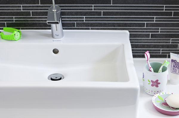 Jednoduché čisté tvary  spoľahlivo dodali  kúpeľni  eleganciu. Pravouhlé umývadlá dopĺňajú striedme moderné batérie so širokým prúdom vody (Hansa), tmavé obkladačky vytvárajú na stene jemný geometrický vzor. Ich dekoračný účinok podporila kontrastná farba a opakovanie štruktúry drevenej podlahy.