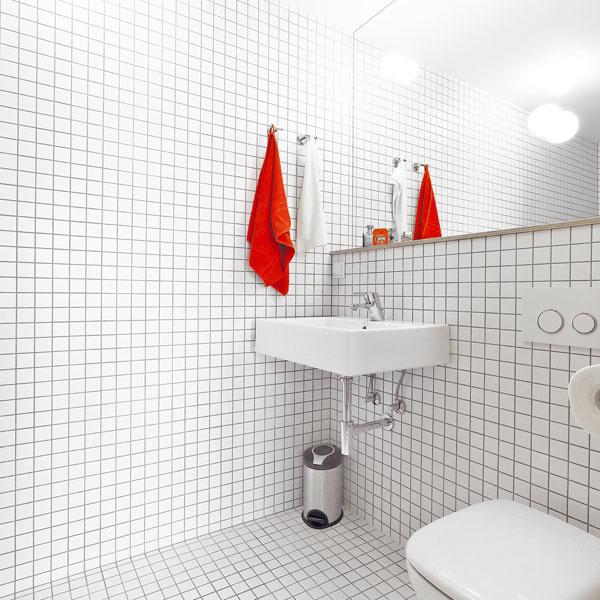 Jednoduchú bielu kúpeľňu oživuje tmavá škárovka – ako hovoria architekti, dodáva jej dynamickosť. Vkúpeľni je toaleta ahlboký otvorený sprchovací kút.