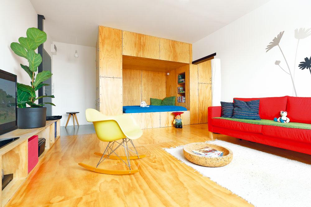 """Použitie borovicovej preglejky na """"Skrini"""", podlahe aj na nízkej polici celý priestor izby zjednotilo. Dizajnové kúsky nábytku mu dodávajú dynamiku."""
