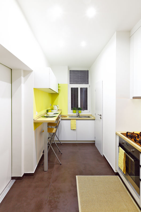 """Drez avarná doska na opačných koncoch kuchyne síce pôsobia zvláštne, vskutočnosti však nie sú od seba veľmi ďaleko – určite nie ďalej ako pri bežnej rohovej linke. Pracovná plocha medzi nimi je však prerušená stenou, čo vytvára najmä psychologickú bariéru. Užívateľ bytu je ale susporiadaním kuchyne spokojný: """"Pracovná plocha je šikovne pri chladničke aj pri varnej doske akdrezu to nie je ďaleko. Drez je zasa pri jedálenskom pulte, takže to nemáme ďaleko so špinavými taniermi,"""" hovorí."""