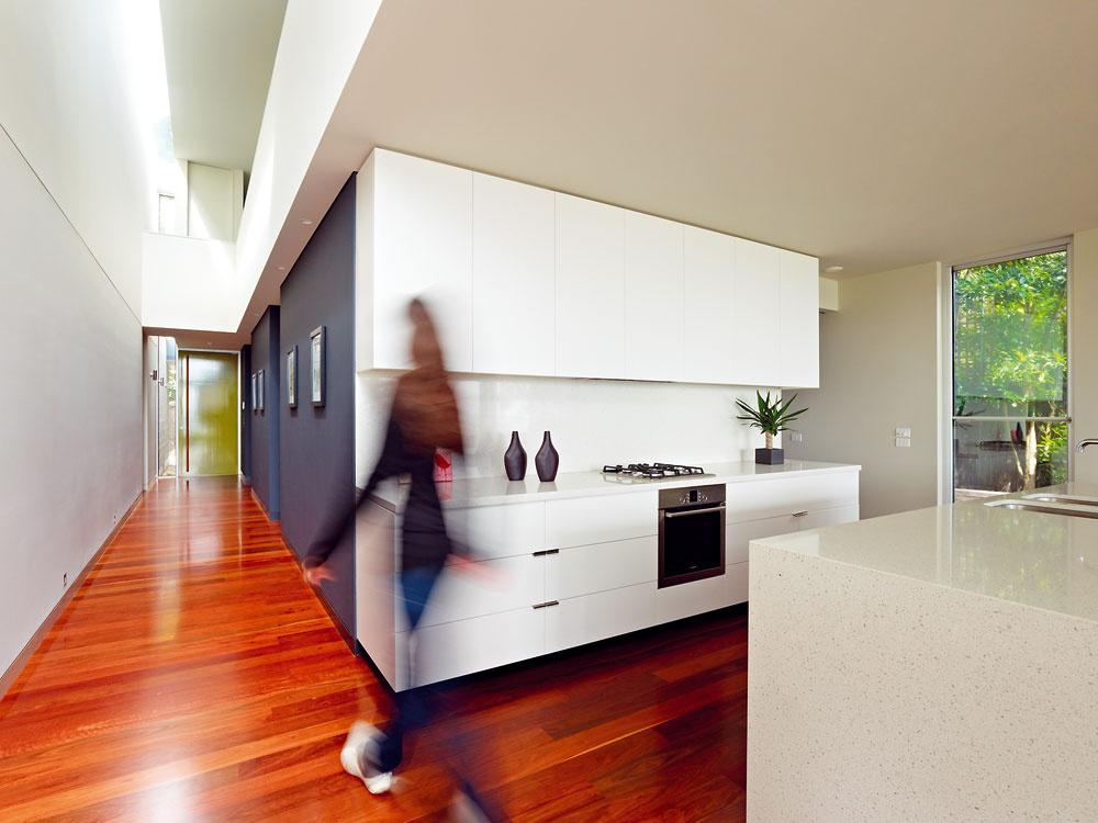 """Nápadný efekt """"vrstvenia"""" vytvára strop prerušený svetlíkom, bok kuchynskej steny, priečka vhale, bariéra galérie ijej podhľad, kde """"vrstvy"""" podfarbuje bodové osvetlenie."""