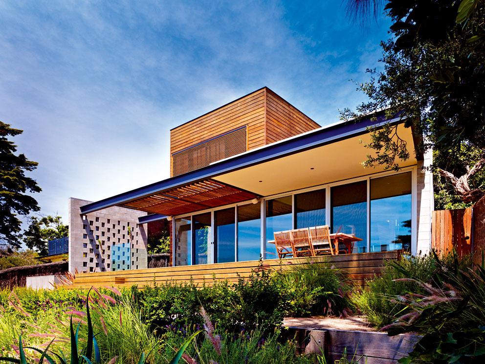 Asymetrický dom na úzkej, nepravidelnej parcele vyvažuje konštrukcia zastrešenia terasy. Kompozícii prispôsobil architekt aj rozmery stupňov, ktoré znej vedú do záhrady.