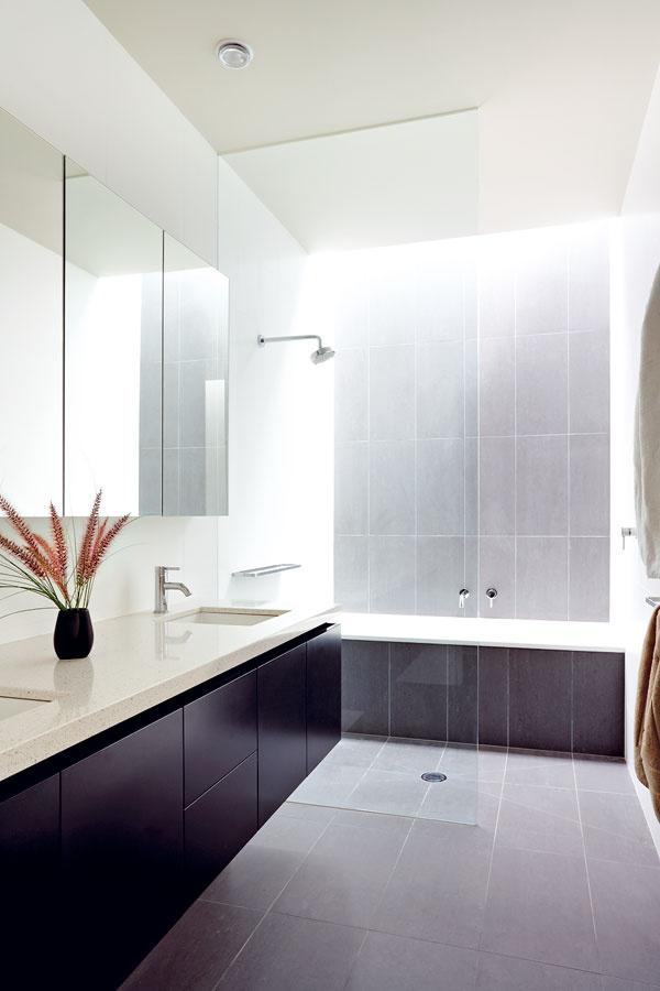 Obe kúpeľne na poschodí sú osvetlené cez úzky svetlík. Kúpeľňa s umývacím pultom z rovnakého materiálu, z akého zhotovili kuchynský ostrov, patrí k detským izbám.