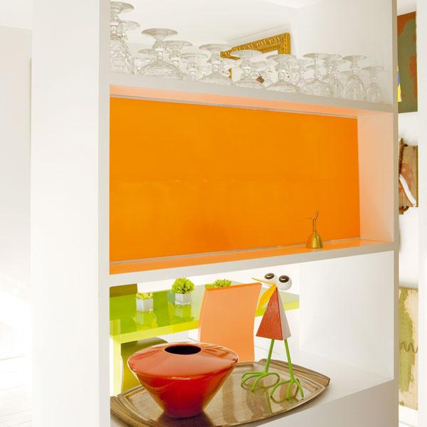 Niektoré police sú prístupné zoboch strán, iné sú zjednej strany uzavreté tabuľami oranžového plastu. Tieto priehľadné farebné akcenty rozjasňujú malý priestor aodkazujú na oranžový nábytok.