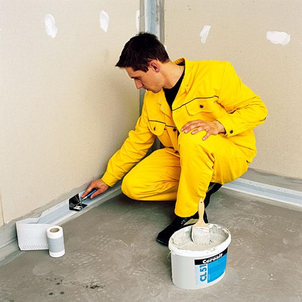 OSADENIE TESNIACEHO PÁSU. Do rohov a dilatačných škár vložte tesniaci pás, ktorý sa vkladá medzi dve vrstvy tesniaceho materiálu. Pružným izolačným pásom prekryte všetky spoje, teda medzi dvoma stenami či stenou a podlahou. Rovnako nevyhnutné je prekryť priestupy inštalácií manžetou a správne utesniť okolie vane.