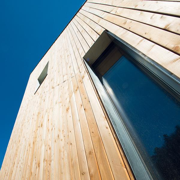 Drevený obklad fasády je premyslený do detailov – napríklad šírka dosiek sa na rôznych plochách líši, čo vytvára dojem nesprávnej perspektívy. Skosenie hrán obkladu sa takisto mení vzávislosti od orientácie na svetové strany – tak, aby bolo drevo čo najviac chránené pred slnkom aprevládajúcimi vetrami.