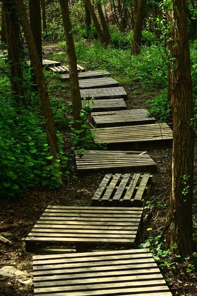 """Tak toto by sme mohli nazvať aj nosením dreva do lesa, čo poviete? No palety sa v tomto prípade celkom rekvalifikovali. Materiálovo sem tiež zapadli a tvar ich predurčoval na """"schodíkové"""" kreácie, ale latkovaný povrch s medzerami by nám mohol robiť starosti. V záhrade, kde nie je príliš hustá premávka nôh, čo by sa mohli potknúť, je to fajn. Na lesnej cestičke plnej turistov je to asi iné..."""