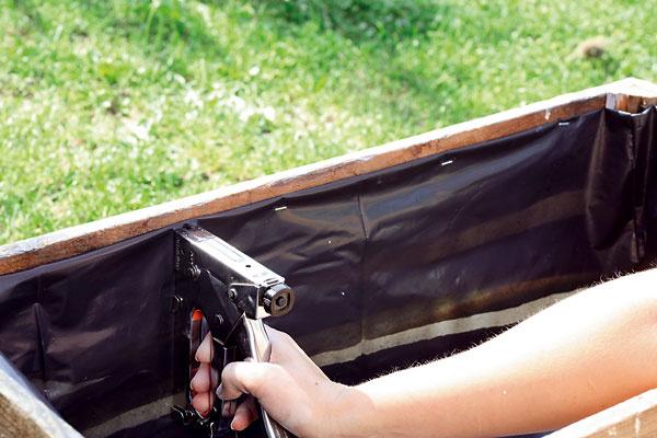 Vnútro debničky vyplňte pevnejšou čiernou fóliou. Na jej pripevnenie použite zošívačku. Na dne urobte dierky na odtekanie vody.
