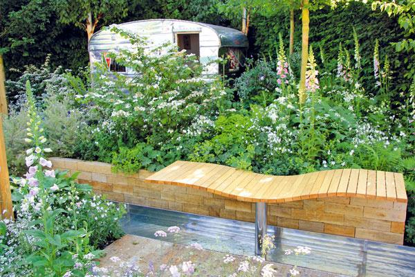 Atraktívnym miestom na relaxovanie sú vtejto záhrade dve drevené ležadlá. Pod jedným znich preteká umelý potok tečúci vkovovom žľabe.