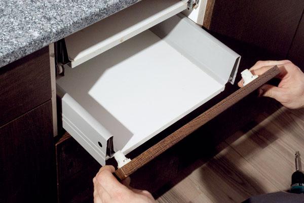 Namontujte čelá zásuviek. Miesto na vyvŕtanie otvorov si jednoducho naznačíte tak, že zásuvku zasuniete, na čielko nanesiete prúžok obojstrannej lepiacej pásky apevne pritlačíte. Na vytlačených miestach potom navŕtajte dierky na skrutky.