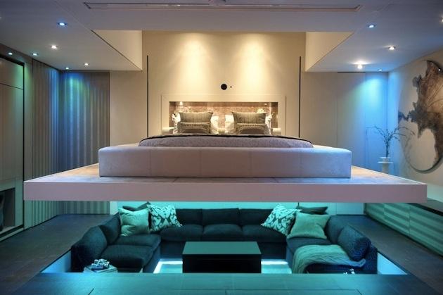 """Modernizujeme ďalej a viac. Miesto, na ktorom každý vidí na každého, má čisto hranatý pôdorys. Efekt sedenia v jame sa ešte posilnil umiestnením pod """"posteľou voľne sa vznášajúcou v priestore"""". Atmosféra tvorená oparom z modrého LED podsvietenia k rozhovoru z 21. storočia patrí. Kompozícia je zaujímavou ukážkou originálneho usporiadania funkčných zón a dôkazom, že komunikačné sedenie sa v súčasnom interiéri nestratí, naopak, hrá tam stále dôležitú úlohu..."""